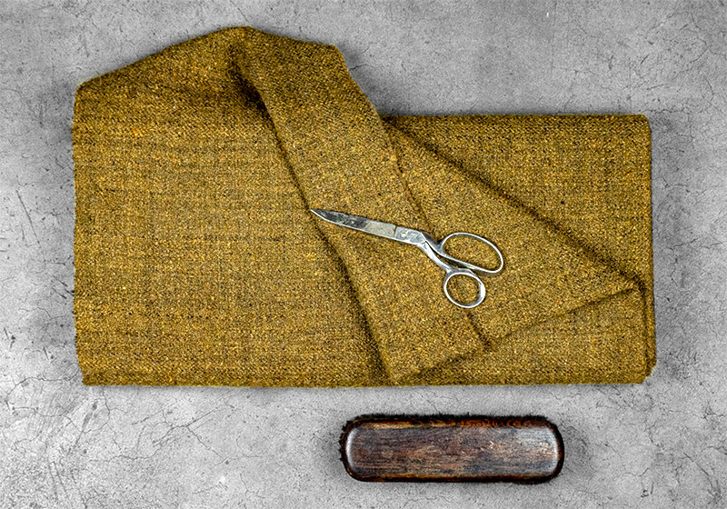 Bolt of wool fabric with scissors and brush