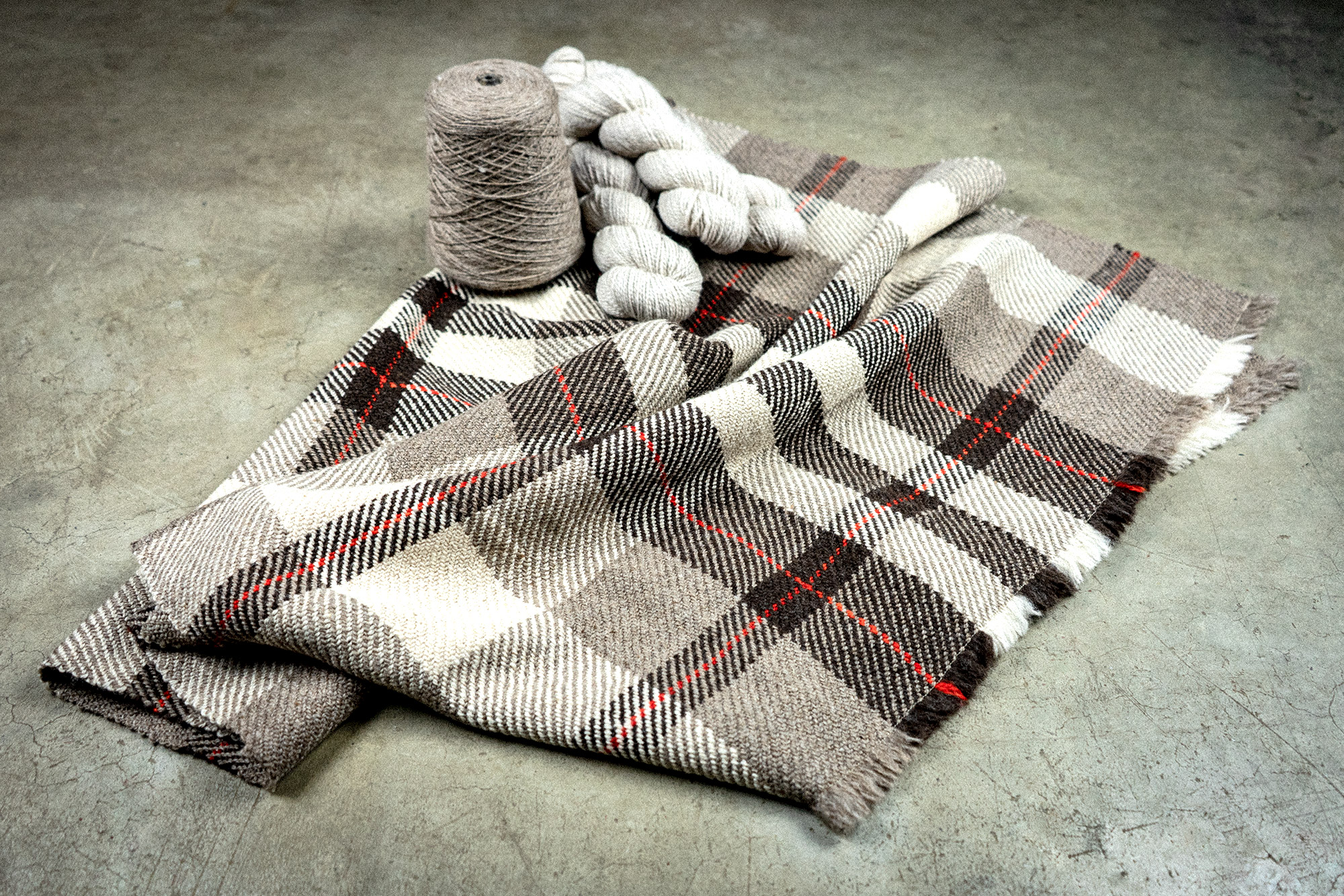 Brown plaid blanket & yarn for knitting and weaving.